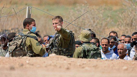 Los soldados israelíes registran a los trabajadores palestinos, que trabajan en Israel, antes de permitirles cruzar a través de un agujero en una valla de seguridad en la ciudad cisjordana de Jenin, luego de la fuga de seis palestinos de una prisión israelí.