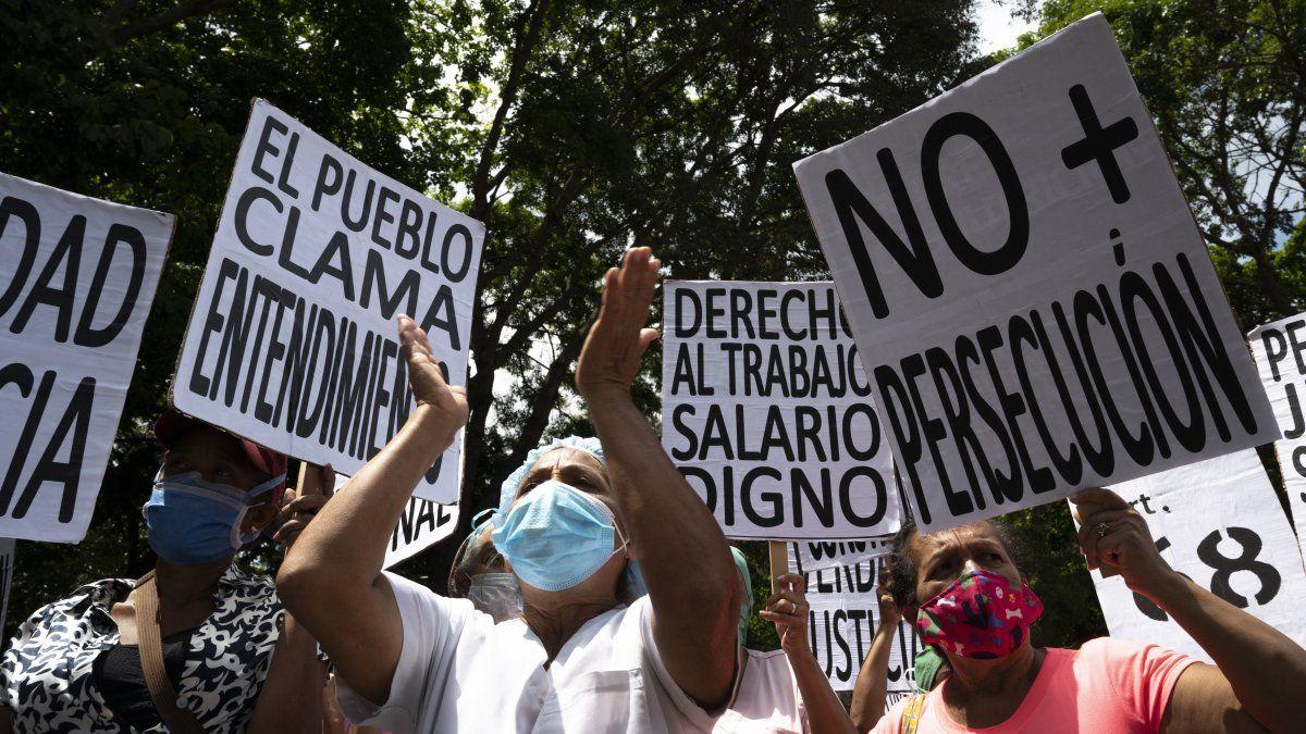 Los trabajadores de la salud de Venezuela portan carteles mientras participan en una protesta exigiendo mejores salarios, vacunación masiva contra el nuevo coronavirus, COVID-19, y material de bioseguridad para protegerse.