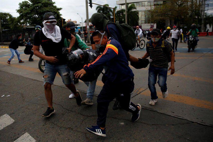 Manifestantes cargan un herido presuntamente por disparo de arma de fuego durante enfrentamientos con la policía este viernes