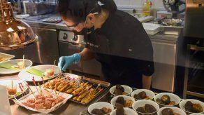 Una mujer prepara muestras de comida a base de vegetales en Satay vegetariano, un laboratorio de especialidades en Singapur, el 21 de abril de 2021.