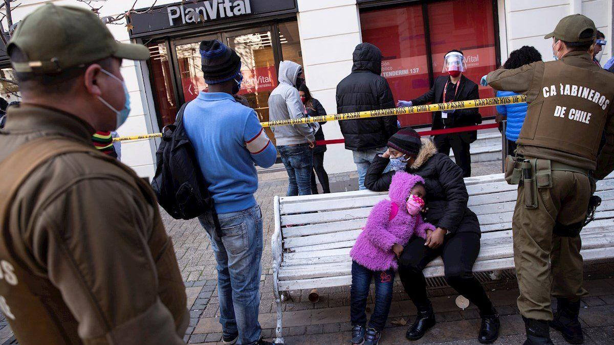 Fotografía de archivo fechada el 30 de julio de 2020, que muestra a un grupo de personas mientras esperan, custodiados por la policía, para realizar los trámites de retiro anticipado del primer 10% de sus fondos de pensiones.
