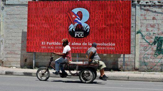 Dos personas pasan hoy frente a una valla que promociona el VIII Congreso del Partido Comunista de Cuba (PCC), a celebrarse del 16 al 19 de abril en La Habana.