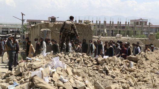 El personal de seguridad y los residentes se reúnen un día después en el lugar de un atentado con coche bomba en el que al menos 24 personas murieron y casi 110 resultaron heridas, en Afganistán.