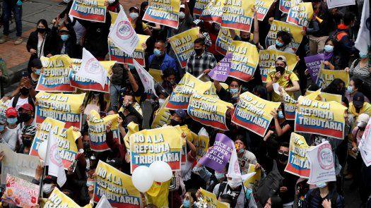 Decenas de personas entre las que sobresalen carteles de protesta participa en la jornada de manifestaciones denominada Paro Nacional, convocada en todo el país para rechazar, entre otros, la reforma tributaria del Gobierno.