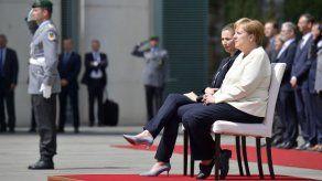 Merkel participa sentada en honores militares para evitar un nuevo temblor