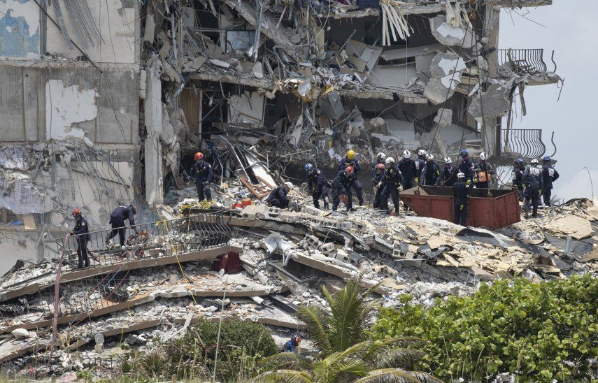 Miembros del equipo de Búsqueda y Rescate Urbano del Sur de Florida buscan posibles sobrevivientes en el edificio de condominios Champlain Towers South de 12 pisos parcialmente derrumbado.