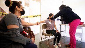 Una joven de 21 años recibe una dosis de vacuna contra COVID-19 en Los Ángeles.