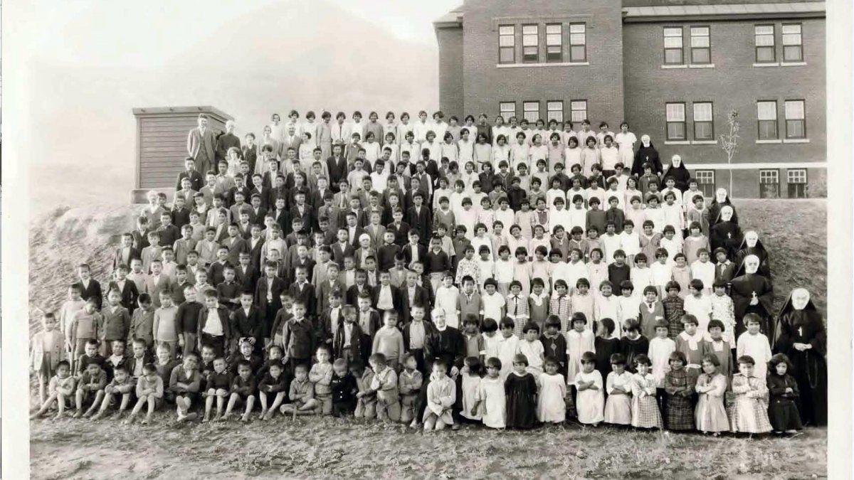 Fotografía sin fechar cedida por el Centro Nacional para la Verdad y la Reconciliación (NCTR) de Canadá donde aparecen niños indígenas y personal religioso mientras posan en las afueras de la Escuela Residencial de Kamloops en la Columbia Británica, Canadá.