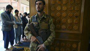 Personal de seguridad de Afganistán se mantiene en guardia mientras devotos musulmanes oran en una mezquita.