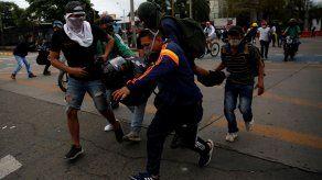 Manifestantes cargan un herido presuntamente por disparo de arma de fuego durante enfrentamientos con la policía este viernes, en una jornada de protestas en el marco del Paro Nacional, en Cali.